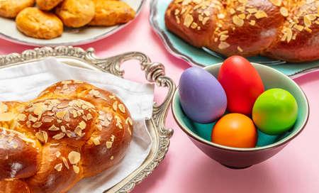 Easter eggs and tsoureki braid, greek easter sweet bread, on pink color background