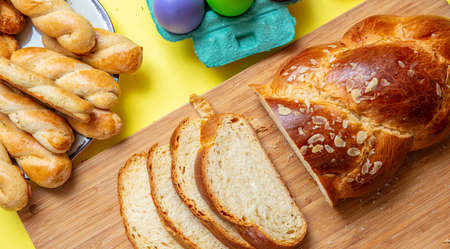 Easter eggs and sliced tsoureki braid, greek easter sweet bread, on wood, yellow color background, top view