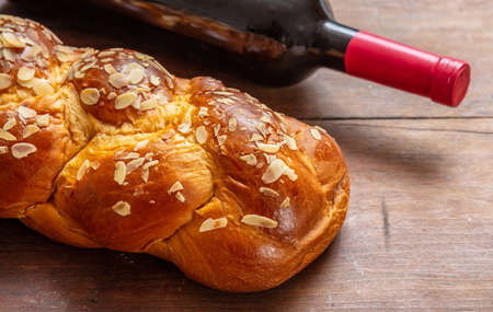 Shabbat concept, challah bread with a bottle of red wine on wooden table, view from above
