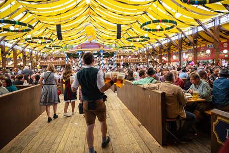 October 7, 2018. Munich, Germany, Oktoberfest, Waiter in tyrolean costume holding beers, tent interior background Sajtókép