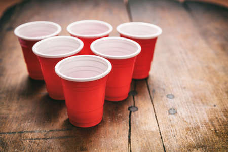 Beer pong, college party game. Plastic red color cups in a triangle shape on wooden background