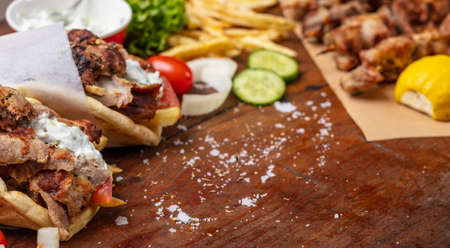 Gyro pita, shawarma, souvlaki. Traditional turkish, greek meat food. Two pita bread wraps and meat skewers on wooden table, copy space Stock Photo