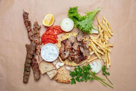 Shawarma, gyros, kebab, souvlaki on pita bread, vegetables and tzatziki sauce, top view. Traditional turkish, greek meat food.