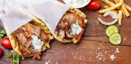Gyro pita, shawarma, take away, street food. Two pita bread wraps with meat, traditional greek turkish food on wooden table, banner