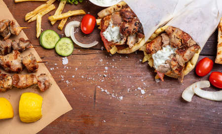 Gyro pita, shawarma, souvlaki. Traditional turkish, greek food. Two pita bread wraps and meat skewers on wooden table, copy space, top view Banque d'images