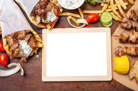 Gyro pita, shawarma. Two pita bread wraps with meat, and blank board on wooden table, space for text