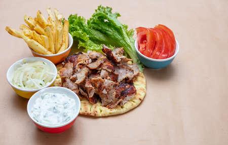 Gyro pita ingredients. Shawarma, gyros, pita bread, vegetables and tzatziki sauce, copy space. Traditional turkish, greek meat food.