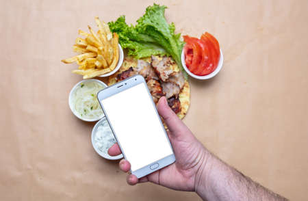 Gyros and smartphone. Hand holding a mobile phone with blank white screen, gyro pita ingredients background, copy space. Online order concept Stock Photo