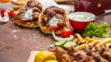 Gyro pita, shawarma, souvlaki. Traditional turkish, greek meat food.Two pita bread wraps and meat skewers on wooden table, copy space