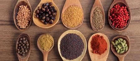 Spezie ed erbe aromatiche. Spezie colorate su tavola di legno, banner, vista dall'alto