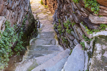 Greece, Kea island. Capital city of Ioulis narrow street with stairs and traditional stone walls