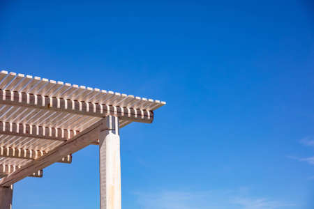 White wooden pergola for sun protection, clear blue sky background, copy space, closeup view Stok Fotoğraf