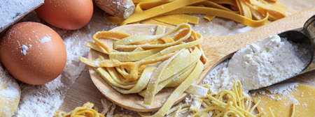 Pasta homemade preparation, ingedients, Fresh tagliatelle pasta, flour and eggs closeup view, banner