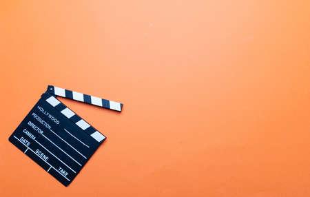 Cinama film concept. Movie clapper board on orange color background, copy space