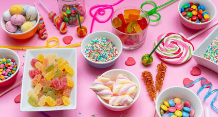 Candies assortment on pink color background, closeup view. Kids birthday party concept
