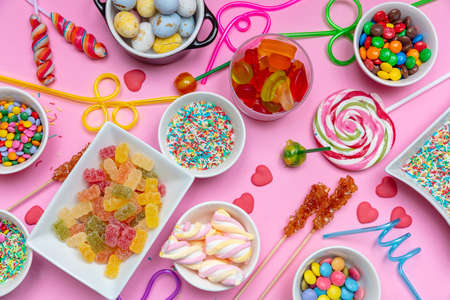 Candies assortment on pink color background, top view. Kids birthday party concept