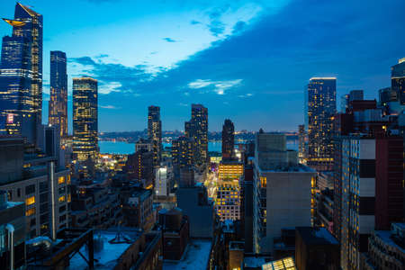 New York city skyline. Aerial view of Manhattan skyscrapers illuminated, Hudson river and blue sky after the sunset