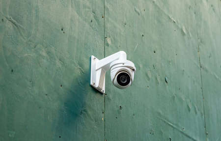 CCTV Security system. Surveillance Camera on a green color wall background, low angle closeup view