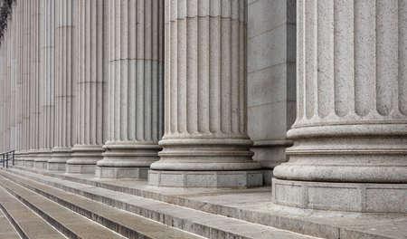 Detalle de columnata y escaleras de piedra. Fila de pilares clásicos en la fachada de un edificio