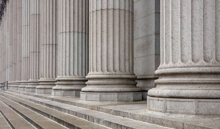Kamienna kolumnada i szczegóły schodów. Klasyczny rząd filarów w elewacji budynku