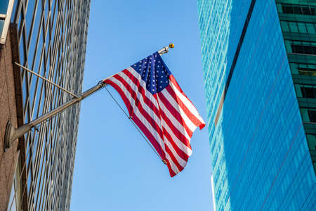 USA symbol in New York streets. American flag in Manhattan downtown, glass skyscrapers background