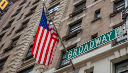 Broadway street sign. Blur American flag and buildings facade background, Manhattan New York downtown