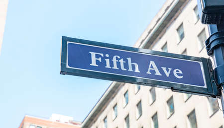 Fifth ave street sign, Manhattan New York downtown. Blue sign on blur buildings facade and blue sky background,