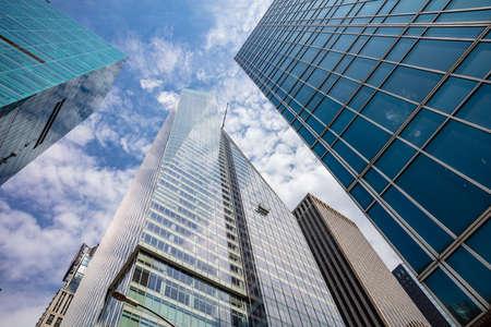 New York, Manhatten. Wolkenkrabbers perspectief weergave tegen blauwe hemelachtergrond, lage hoekmening, glazen ramen schoonmaakdiensten