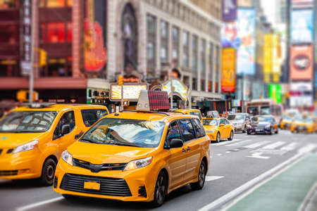 New York, Times square. Broadway streets. High buildings, colorful neon lights, large commercial ads, cars and traffic