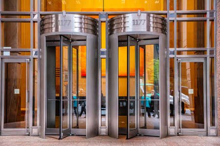 New York, USA. May 2nd, 2019. Revolving doors, stainless steel, on glass building facade, Manhatan downtown