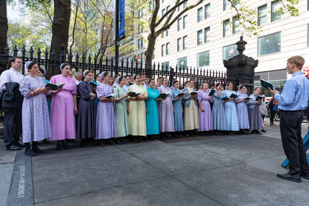 USA, New York, May 4, 2019. Choir singing outdoors on the street in a spring day. Women wearing traditional pastel colors dresses Editorial