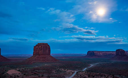 Monument Valley, Fullmoon in spring. Red rocks against blue sky in the evening. Navajo Tribal Park in the Arizona-Utah border, United States of America.