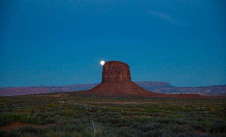 Monument Valley, Fullmoon in spring. Red rocks against dark blue sky. Navajo Tribal Park in the Arizona-Utah border, United States of America.