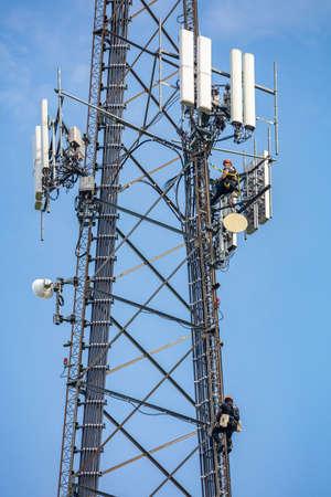 Canton, Ohio lake, USA. May 8, 2019. Communication maintenance. Two technicians climbing on telecom tower antenna against blue sky background
