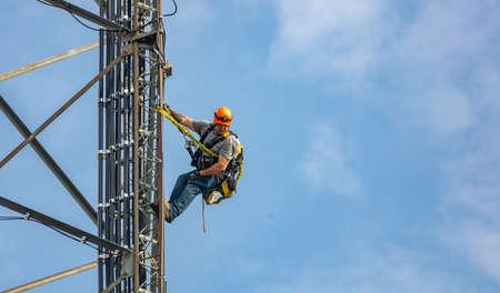 Canton, Ohio lake, USA. May 8, 2019. Communication maintenance. Technician climbing on telecom tower antenna against blue sky background, copy space