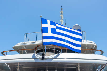 Greek flag on luxury yacht stern. Ongoing cruise to Greece. Clear blue sky background, close up view.
