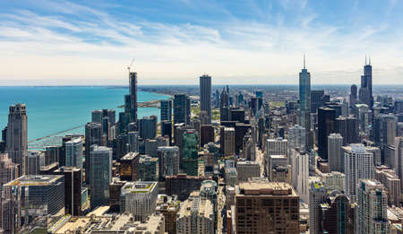 Chicago cityscape aerial view, spring day. High rise buildings and lake Michiganl, blue sky background. High angle view from skydeck