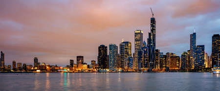 Chicago skyline panorama, sunset time. Panoramic view of Chicago city waterfront illuminated skyscrapers, cloudy sky in the evening