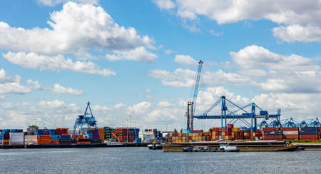 Rotterdam harbor, Netherlands. July 2nd, 2019. Logistics business. Huge bridge cranes and stacked containers, international port of Rotterdam, sunny summer day Redactioneel