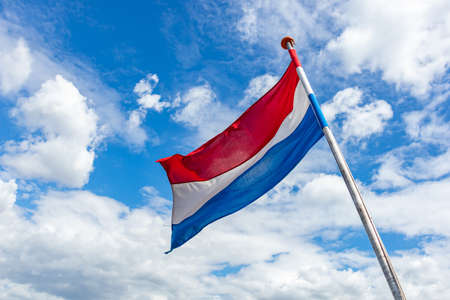 Netherlands flag. Dutch national symbol waving on pole against blue sky with clouds, sunny day