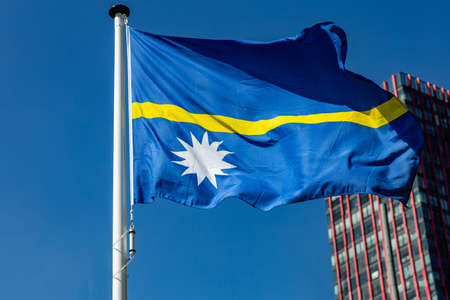Nauru flag. National symbol waving on pole, Highrise building and clear blue sky background, sunny day. Indepedence day concept. Stockfoto