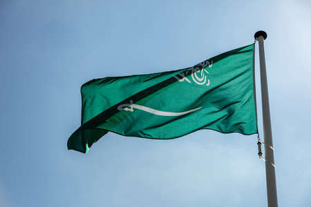 Saudi Arabia flag, National symbol waving against clear blue sky, sunny day Stok Fotoğraf