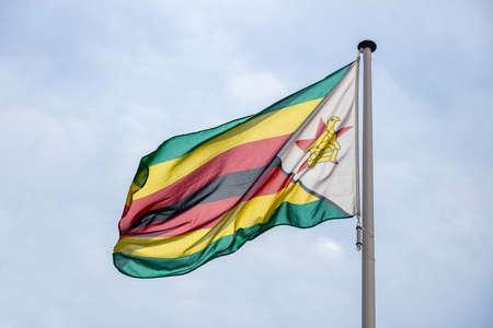 Zimbabwe flag, National symbol waving against clear blue sky, sunny day Banco de Imagens