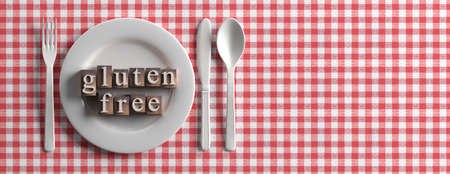 Gluten free menu, healthy eating concept. Gluten-free text on a plate, rustic red checkered tablecloth, banner, copy space. 3d illustration