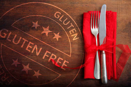 Gluten free certified menu, healthy eating concept. Gluten-free stamp and cutlery set on rustic wooden table, top view.