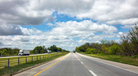 Highway in a sunny spring day, USA. National road, passing through American countryside. Blue cloudy sky background Stock Photo