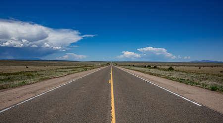 Highway in a sunny spring day, countryside USA. Empty national road, passing through American desert, Blue clear sky background