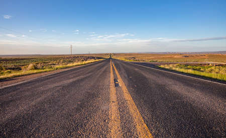 Highway in a sunny spring day, countryside USA. Empty national road, passing through American desert, Blue sky background