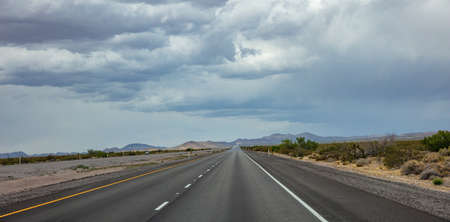 Highway in a sunny spring day, countryside USA. Empty national road, passing through American desert, Blue cloudy sky background