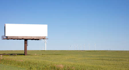 Billboard blank white color, for advertisement on a highway, spring sunny day, wind turbines on a green field and blue sky, copy space
